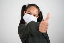 Little girl with medical mask smiles with the thumb up with gesture of hope and victory on a white background. Concept of positivism against the spread of the coronavirus.