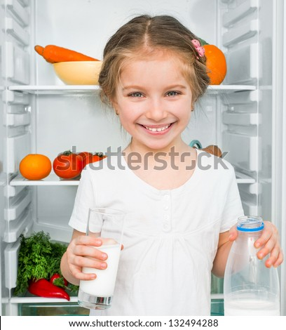 little girl with milk against a refrigerator with food