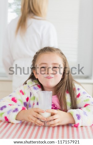 Little girl with milk moustache after drinking glass of milk