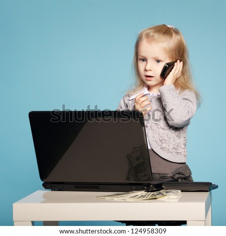 little girl with mobile phone and laptop