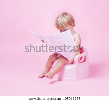 Little girl with newspaper on the pot