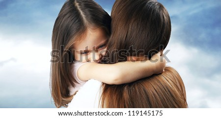 Little girl with nice hair hugs his mother