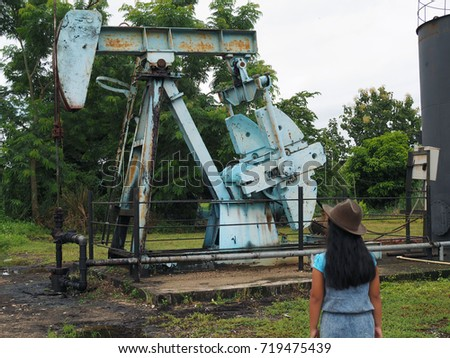 Little girl with Oil Pump Jack (Sucker Rod Beam) on tropical forest background #719475439