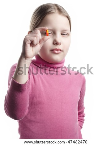 Little girl with orange pill isolated on white - stock photo