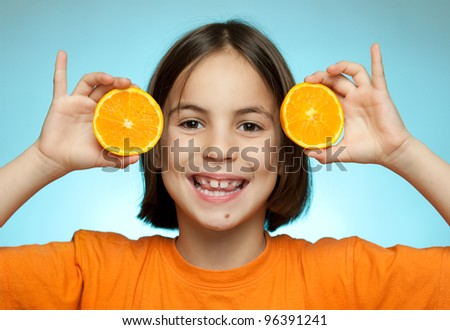 Little girl with oranges on a blue background
