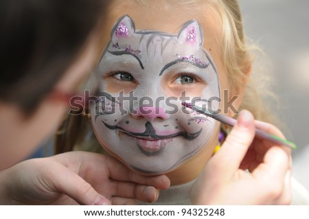 Little girl with painting face as a cat