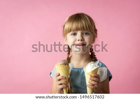 little girl with pigtails in a blue dress eating ice cream in a cone on a pink background