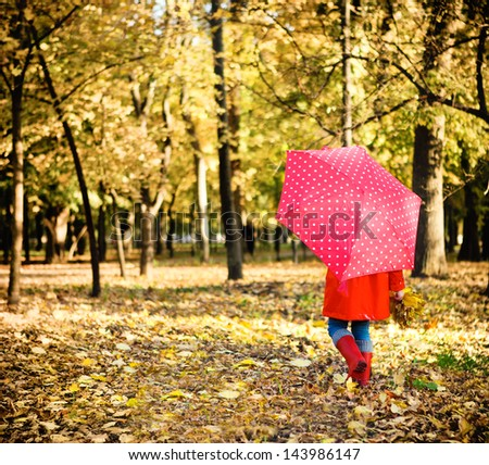 Little girl with polka dots umbrella walking through alley with fall foliage