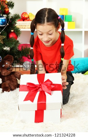 Little girl with present box near christmas tree