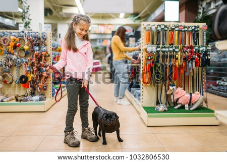 Little girl with puppy in pet shop, friendship