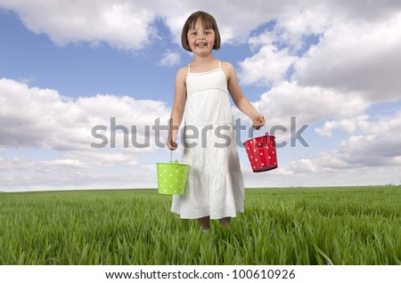 little girl with red and green bucket in meadow