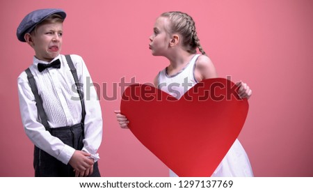 Photo of  Little girl with red paper heart trying to kiss young boy male kid recoils, date