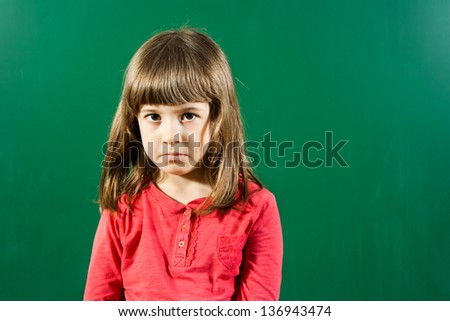 Little girl with sad expression in front of blackboard,Sad little girl