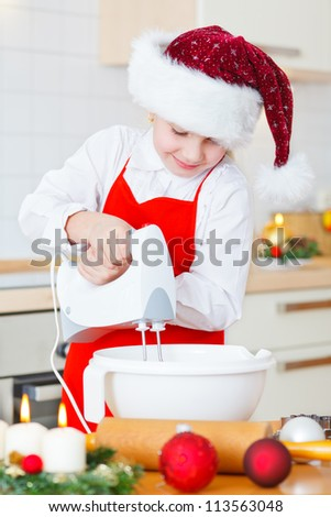 little girl with santa hat at christmas bakery
