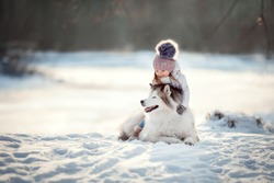 little girl with Siberian husky are walking in the winter forest