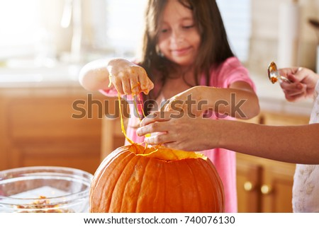 little girl with slime on hands from pumpkin to make jack o lantern for halloween