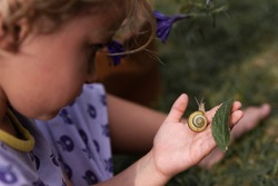 Little girl with snail on a hand outdoor. Mindfulness and focus on wild nature. Macro. Autism child and childhood.