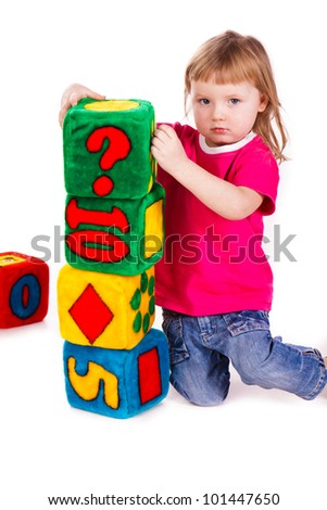 Little girl with soft blocks as a tower isolated on white