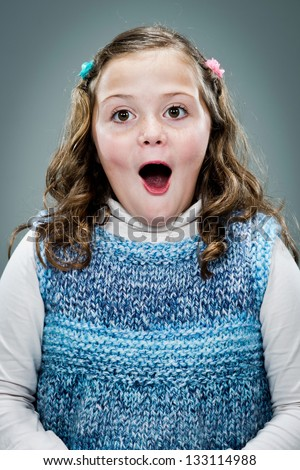 Little Girl with Surprise Expression Over a Grey Background