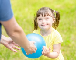 Little girl with syndrome down and her mother play with a ball in a summer park