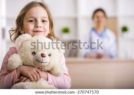 Little girl with teddy bear is looking at the camera. Female doctor on background. #270747170
