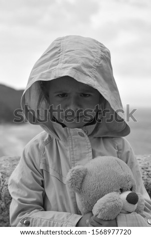 Little girl with teddy bear is wearing a raincoat jacket with hood against a stormy sky. Childhood concepts. Environmental concepts. Climate concepts.