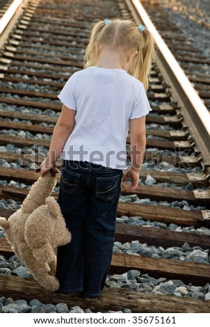 little girl with teddy bear on railroad tracks