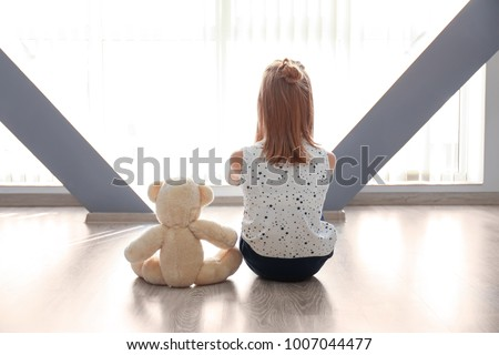 Little girl with teddy bear sitting on floor near window in empty room. Autism concept
