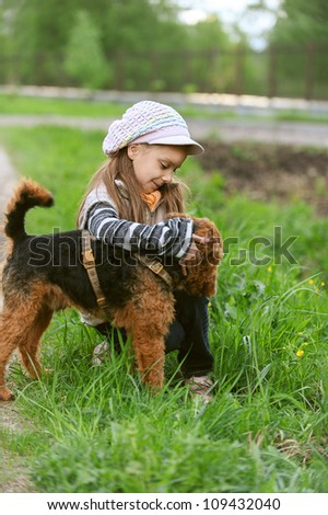 Little girl with terrier in city park.