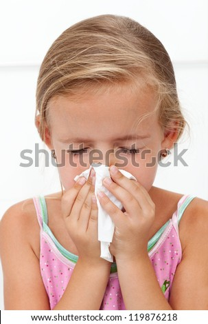 Little girl with the flu blowing nose - closeup