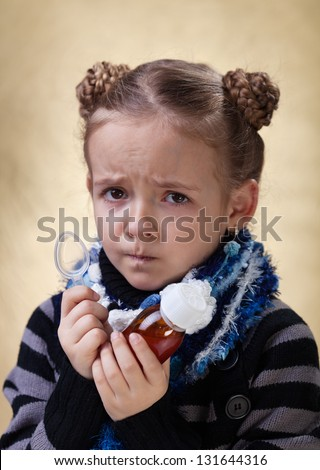 Little girl with the flu - holding cough medicine syrup and looking unhappy