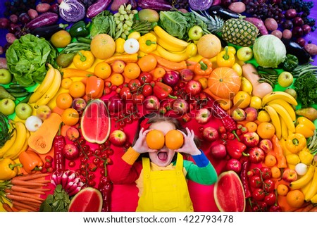 Little girl with variety of fruit and vegetable. Colorful rainbow of raw fresh fruits and vegetables. Child eating healthy snack. Vegetarian nutrition for kids. Vitamins for children. View from above.