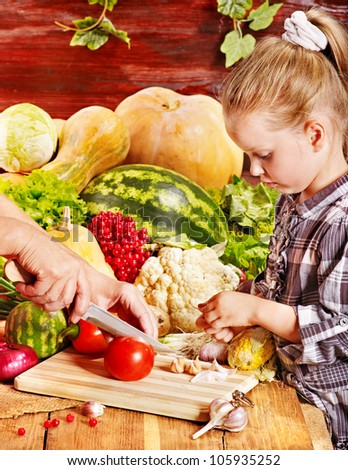 Little girl with vegetable on kitchen.