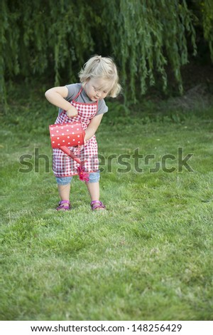 little girl with watering can, outdoors in the garden