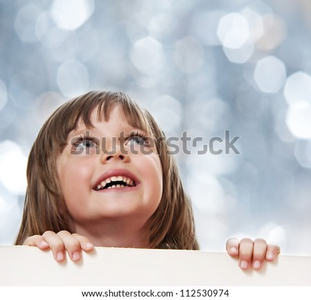little girl with  white board with empty space - bokeh background