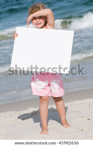 Little girl with whiteboard at the beach