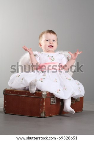 little girl with wings of an angel sits on an old suitcase