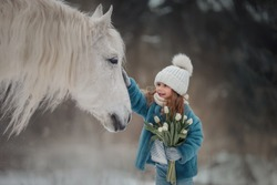 Little girl with with flowers bouquet and white horse in winter forest