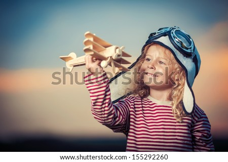 Little girl with wooden plane