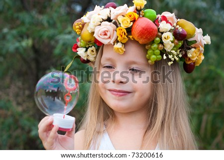 little girl with wreath from flowers blows soap bubbles