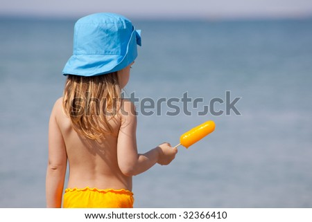 Little girl with yellow ice cream standing over sea at beach