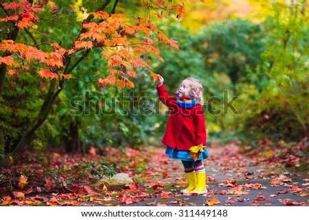 Little girl with yellow leaf. Child playing with autumn golden leaves. Kids play outdoors in the park. Children hiking in fall forest. Toddler kid under a maple tree on a sunny October day.