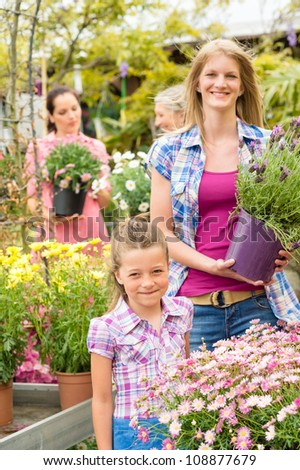 Little girl with young woman buying potted flower at market