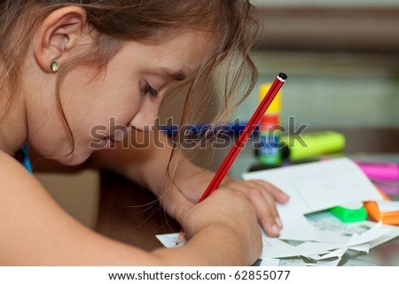 Little girl working on her art project with art materials on the table