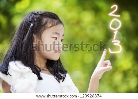 Little girl write the numbers 2013 new year