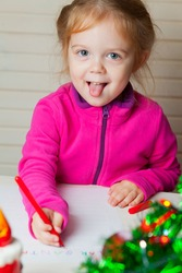 Little girl writes a letter to Santa. A child draws a Christmas drawing. Shows tongue.