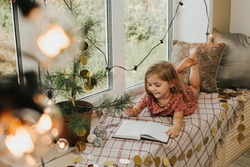 little girl writes in a notebook. The child sits on the windowsill. Christmas and New Year concept. High quality photo
