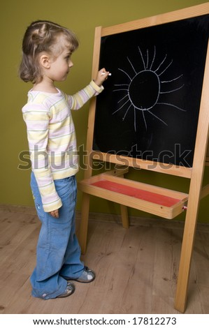Little girl writing and drawing on blackboard; education