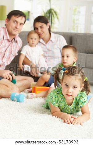 Little girl (3-4 years) lying on floor at home with nuclear family in background.