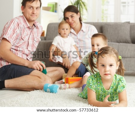 Little girl (3-4 years) lying on floor at home with nuclear family in background.?